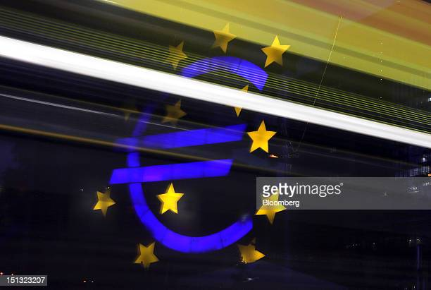 Light trails from passing automobiles are seen in front of the euro sign sculpture outside the headquarters of the European Central Bank in...