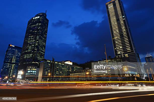Light trails from passing traffic run past the Selamat Datang Monument center left and other buildings at the Hotel Indonesia Roundabout in Jakarta...