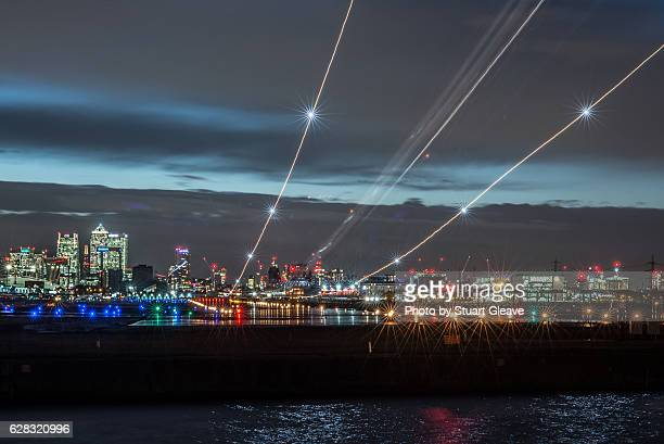 light trails from plane landing at london city airport - london city airport stock pictures, royalty-free photos & images
