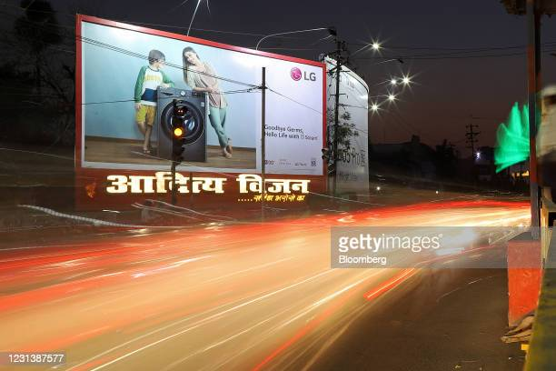 Light trails illuminate a street with an LG Electronics Inc. Billboard advertising one of the company's washing machines in Patna, Bihar, India, on...