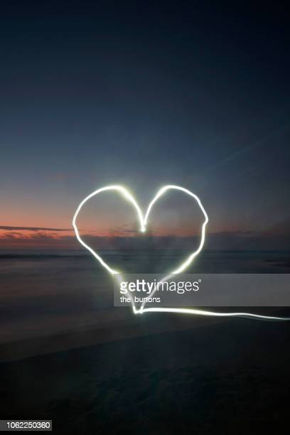 light trails in heart shape at beach during sunset (light painting) - love photos et images de collection