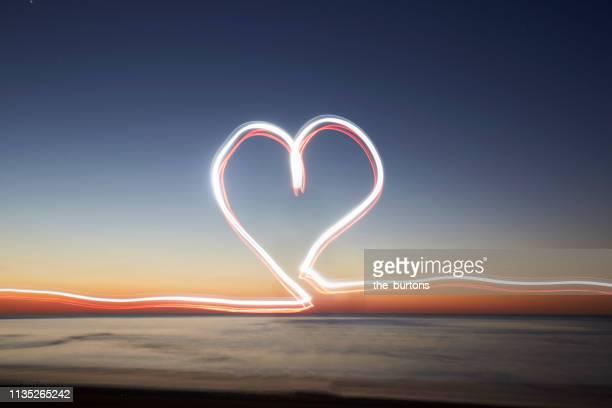 light trails in heart shape at beach during sunset (light painting) - paysage enchanteur photos et images de collection