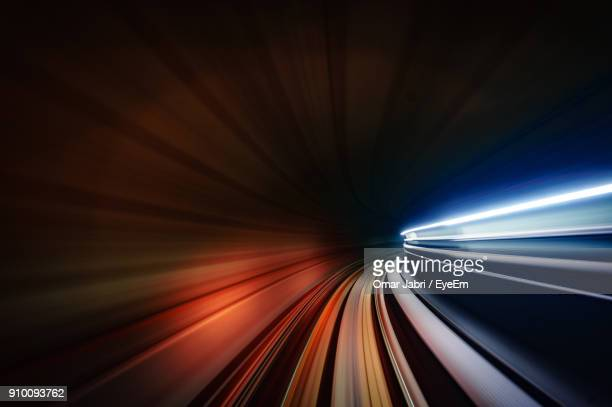 light trails in illuminated tunnel at night - velocidad fotografías e imágenes de stock