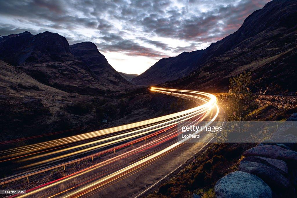 山の中の遠隔道路の夜の光トレイル : ストックフォト