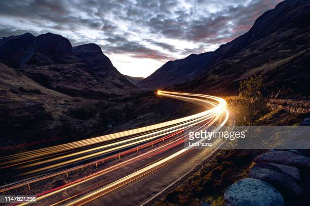 light trails in the night on a remote road in mountains - traffic stock pictures, royalty-free photos & images