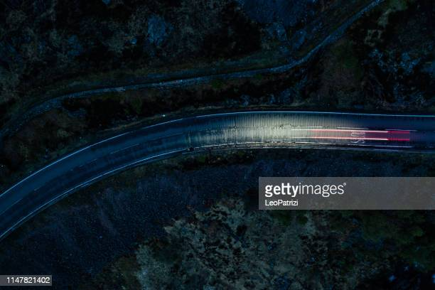 light trails in the night on a remote road in mountains - road stock pictures, royalty-free photos & images