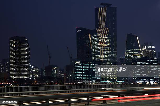 Light trails left by moving traffic run along a bridge over the Han River as commercial buildings stand illuminated in the Yeouido financial district...