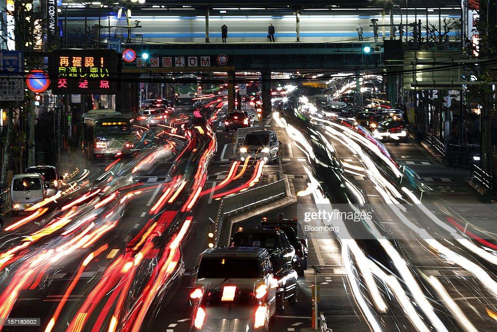 Light trails left by moving traffic run along a road in this long exposure photograph taken in Tokyo, Japan, on Thursday, Nov. 29, 2012. Japan's cabinet approved a second round of fiscal stimulus worth 880 billion yen ($10.7 billion) using budget reserves as Prime Minister Yoshihiko Noda attempts to boost the economy before elections on Dec. 16. Photographer: Kiyoshi Ota/Bloomberg via Getty Images