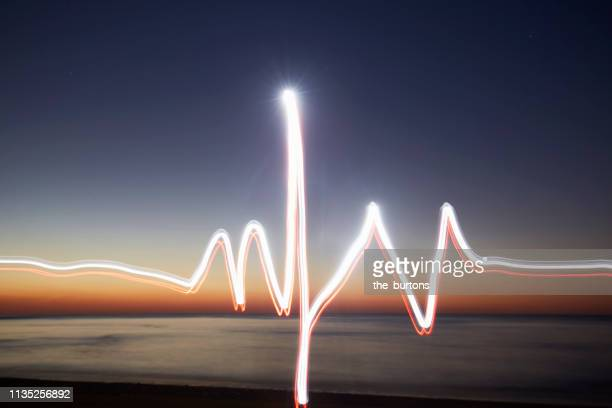 light trails like an electrocardiogram trace (ecg) at beach during sunset (light painting, pulse trace, heart rate line) - lichtspur stock-fotos und bilder