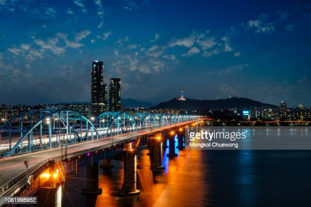 Light trails of car driving on Dongjak bridge cross over Han river into N Seoul Tower at night in Seoul city, South Korea
