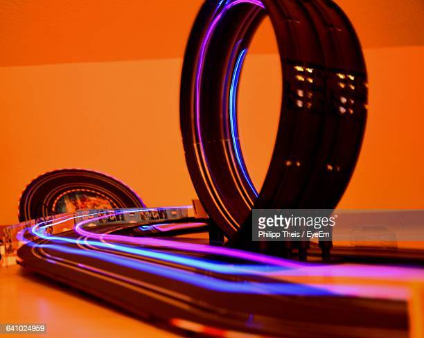 Light Trails Of Electric Slot Cars Against Orange Wall
