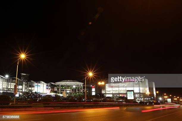 Light trails of passing traffic illuminate a road outside the Aeon Co mall at night in the Long Bien district of Hanoi Vietnam on Thursday July 21...