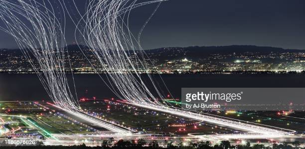 light trails of takeoffs at airport over water - long exposure stock pictures, royalty-free photos & images
