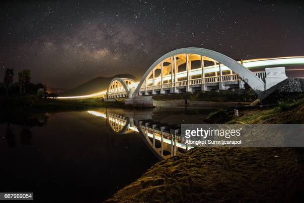 Light trails of train, Milky way and White bridge, Lamphun, Thailand.