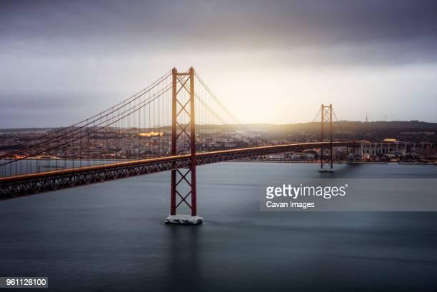 light trails on april 25th bridge over tagus river against cloudy sky during sunset - lisboa fotografías e imágenes de stock