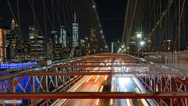 light trails on bridge against buildings at night - jens siewert stock-fotos und bilder
