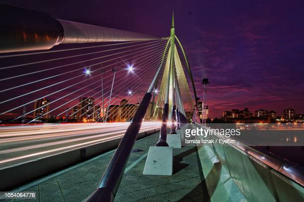 light trails on bridge against sky at night - putrajaya stock photos and pictures