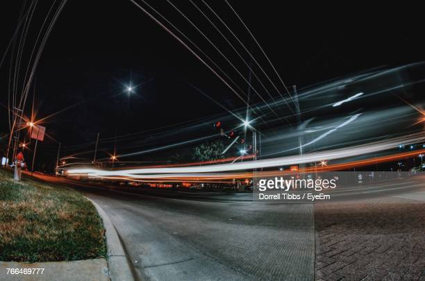 light trails on bridge against sky at night - wichita stock photos and pictures