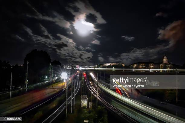 light trails on bridge in city against sky at night - walter ciceri foto e immagini stock
