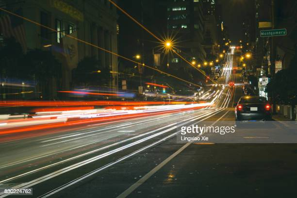 light trails on california street at night, san francisco - vehicle light stock photos and pictures