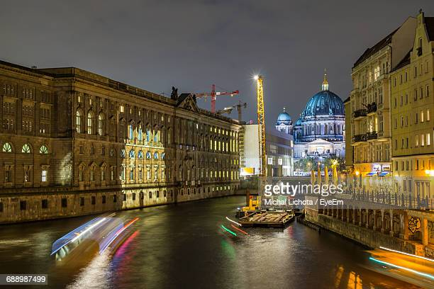 light trails on canal by illuminated berlin cathedral against sky at night - central berlin stock photos and pictures