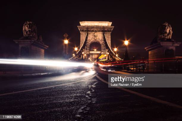 light trails on chain bridge in city at night - lutai razvan stock pictures, royalty-free photos & images