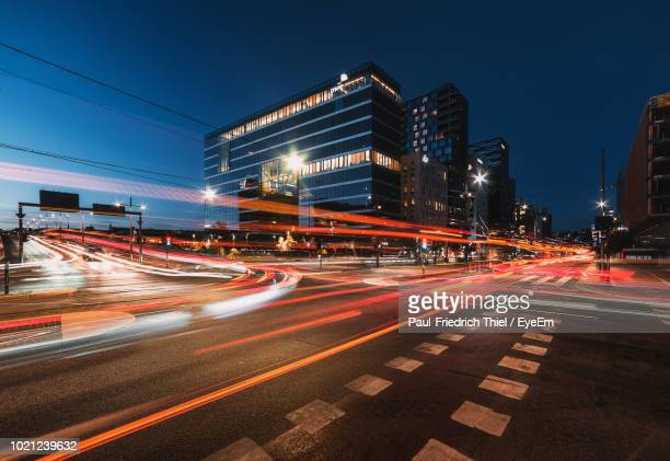 light trails on city street at night - traffic stock pictures, royalty-free photos & images