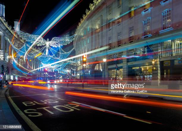 light trails on city street at night - night stock pictures, royalty-free photos & images