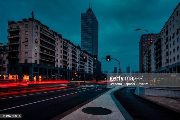 light trails on city street by buildings against sky at dusk milan italy - milan stock pictures, royalty-free photos & images