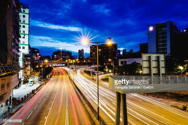 Light Trails On City Street By Buildings Against Sky At Night