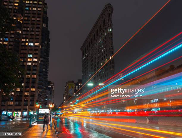 light trails on city street by buildings against sky at night - noam cohen stock pictures, royalty-free photos & images
