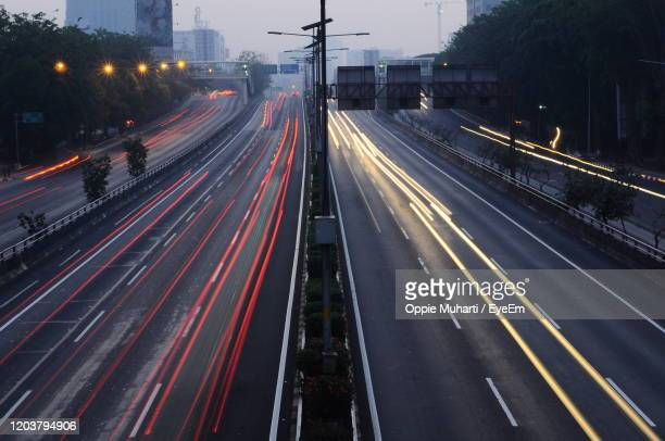 light trails on city street - oppie muharti stock pictures, royalty-free photos & images