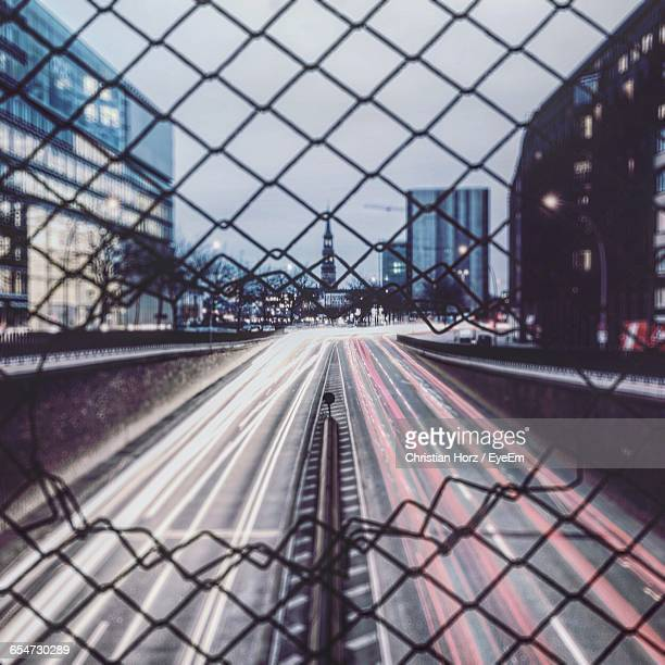 Light Trails On City Street Seen Through Damaged Chainlink Fence