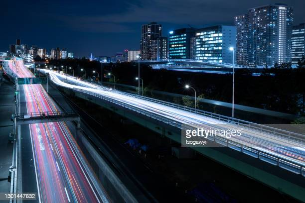 light trails on highway and illuminated buildings at night - isogawyi stock pictures, royalty-free photos & images