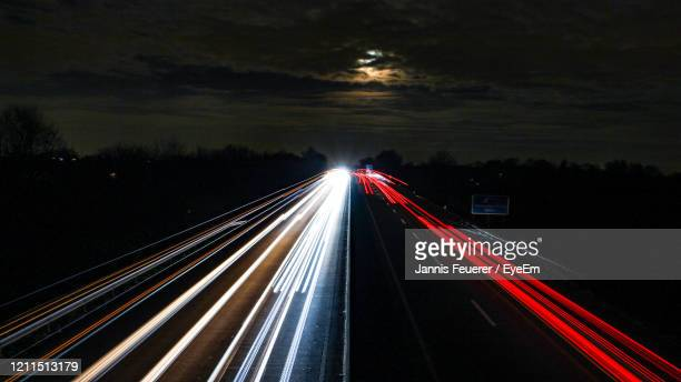 light trails on highway at night - freie straße stock-fotos und bilder