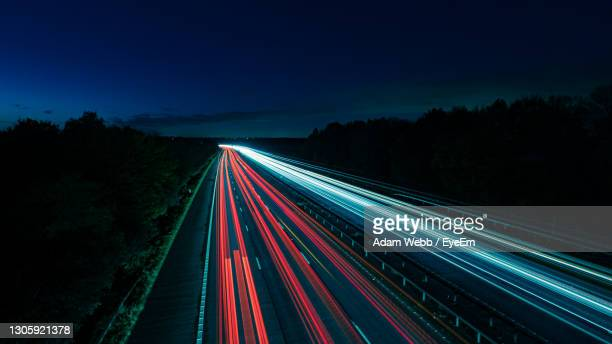 light trails on highway at night - red stock pictures, royalty-free photos & images