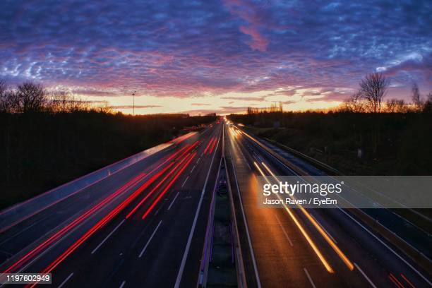 light trails on highway at sunset - northampton stock pictures, royalty-free photos & images