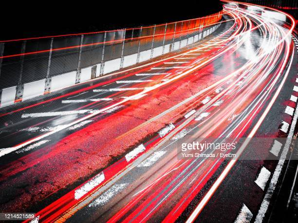 light trails on highway in city at night - sports track stock pictures, royalty-free photos & images