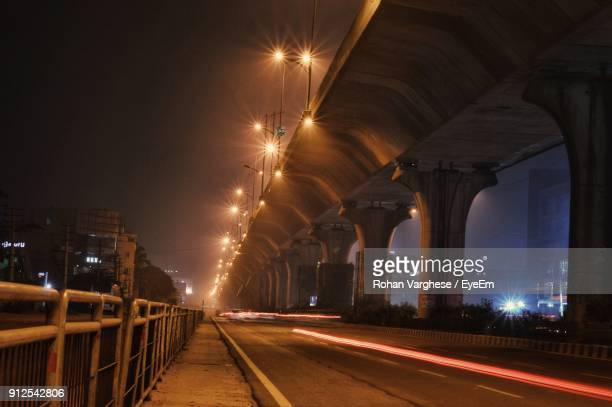 light trails on illuminated city against clear sky at night - bangalore city stock pictures, royalty-free photos & images