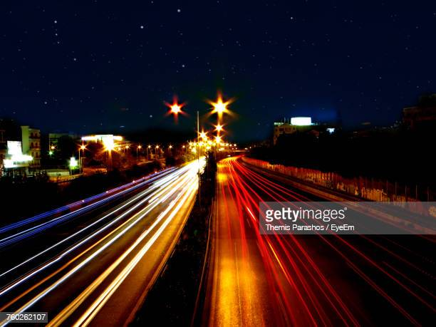 Light Trails On Illuminated City Against Sky At Night