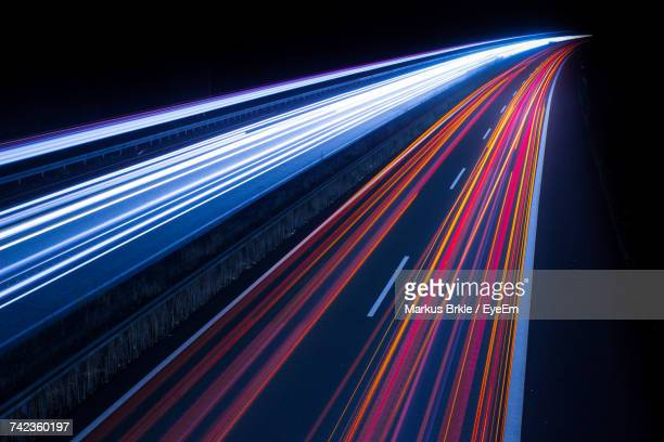 light trails on illuminated city road at night - dividing line road marking stock pictures, royalty-free photos & images