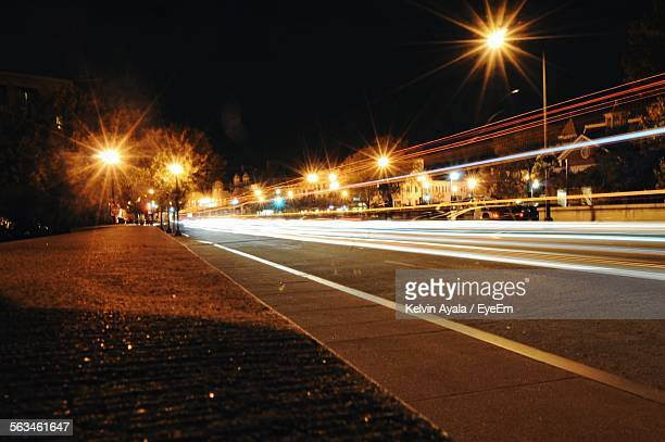 Light Trails On Illuminated Road At Night