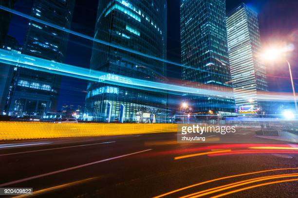 light trails on modern building background in shanghai - lighting equipment stock photos and pictures