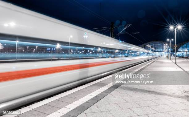 light trails on railroad station platform at night - railway station stock pictures, royalty-free photos & images