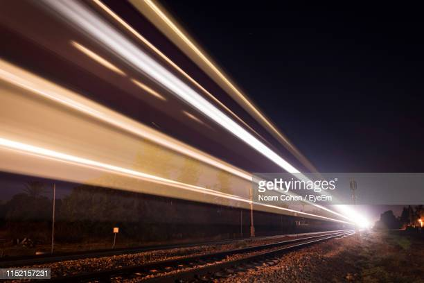 light trails on railroad track at night - noam cohen stock pictures, royalty-free photos & images