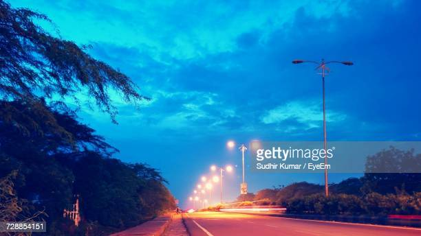 light trails on road against blue sky at night - haryana stock photos and pictures