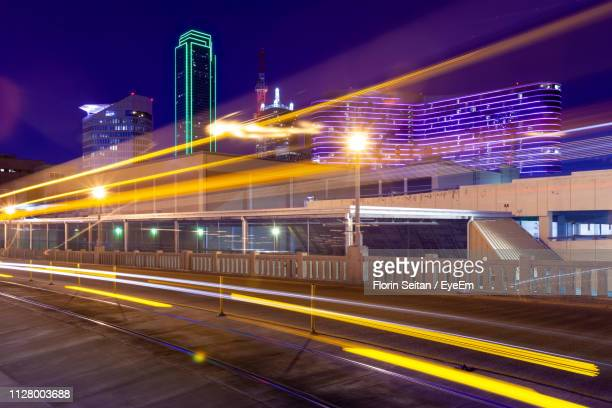 light trails on road against buildings at night - florin seitan stock pictures, royalty-free photos & images