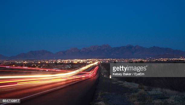 light trails on road against clear blue sky at dusk - las cruces new mexico stock pictures, royalty-free photos & images