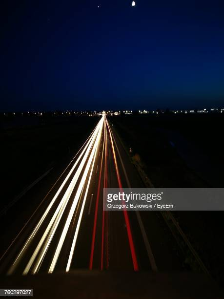 Light Trails On Road Against Clear Blue Sky At Night