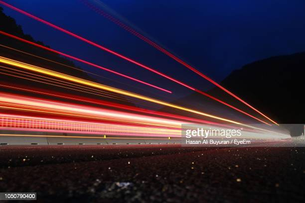 light trails on road against sky at night - tail light stock pictures, royalty-free photos & images
